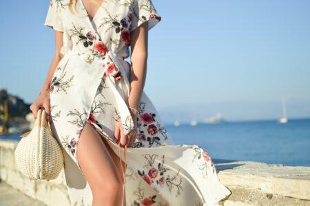 woman walking on seaside while holding woven bag