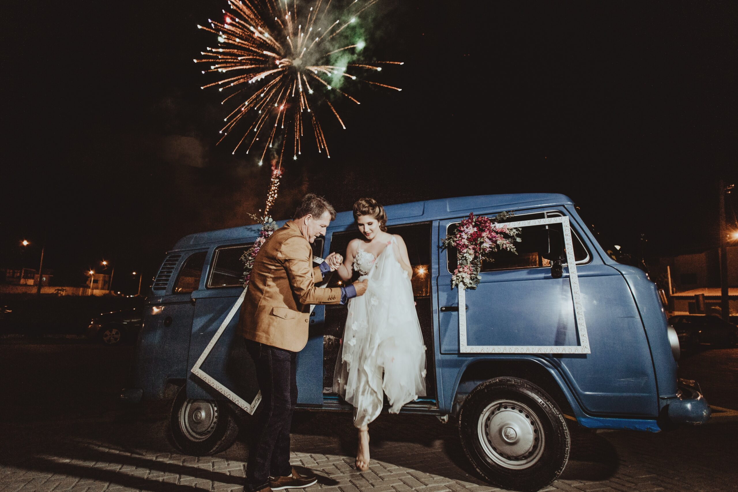 woman getting out of the blue van while holding a man during night time