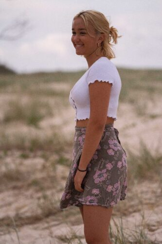 woman in white shirt and purple floral skirt standing on green grass field during daytime