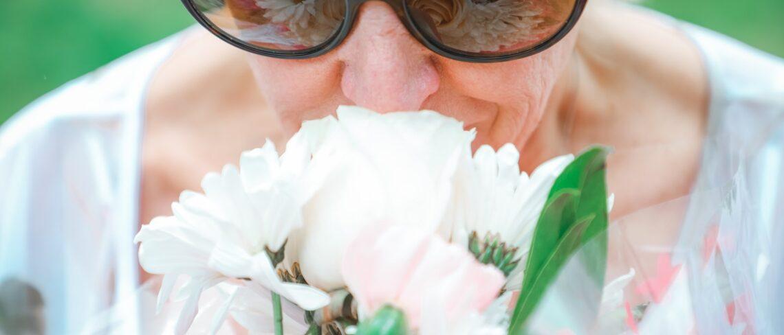 woman in black framed sunglasses holding white flower